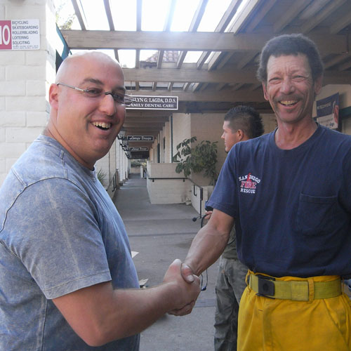 Dr. Klein with firefighter shaking hands